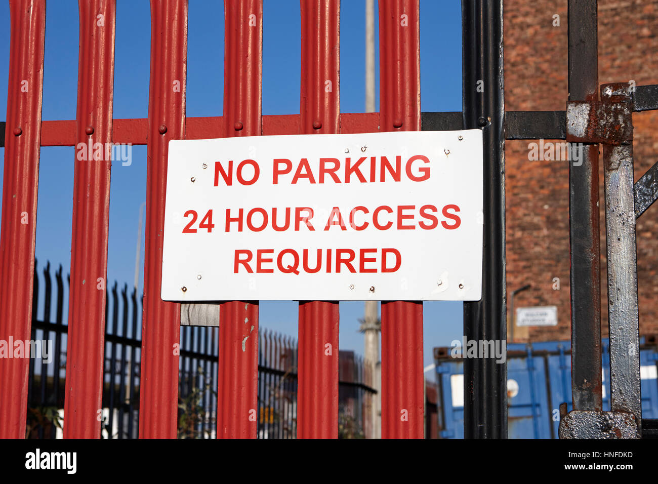 no parking sign 24 hour access required on a fence in the uk - Stock Image