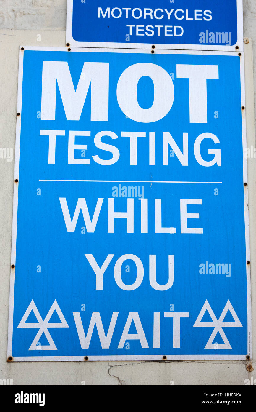 mot testing sign centre while you wait motorcycles tested signs uk - Stock Image
