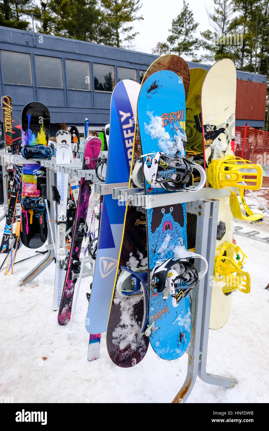 Outdoor ski / snowboard rack with stored snowboarding and skiing equipment at Boler Mountain Ski Club in London, - Stock Image