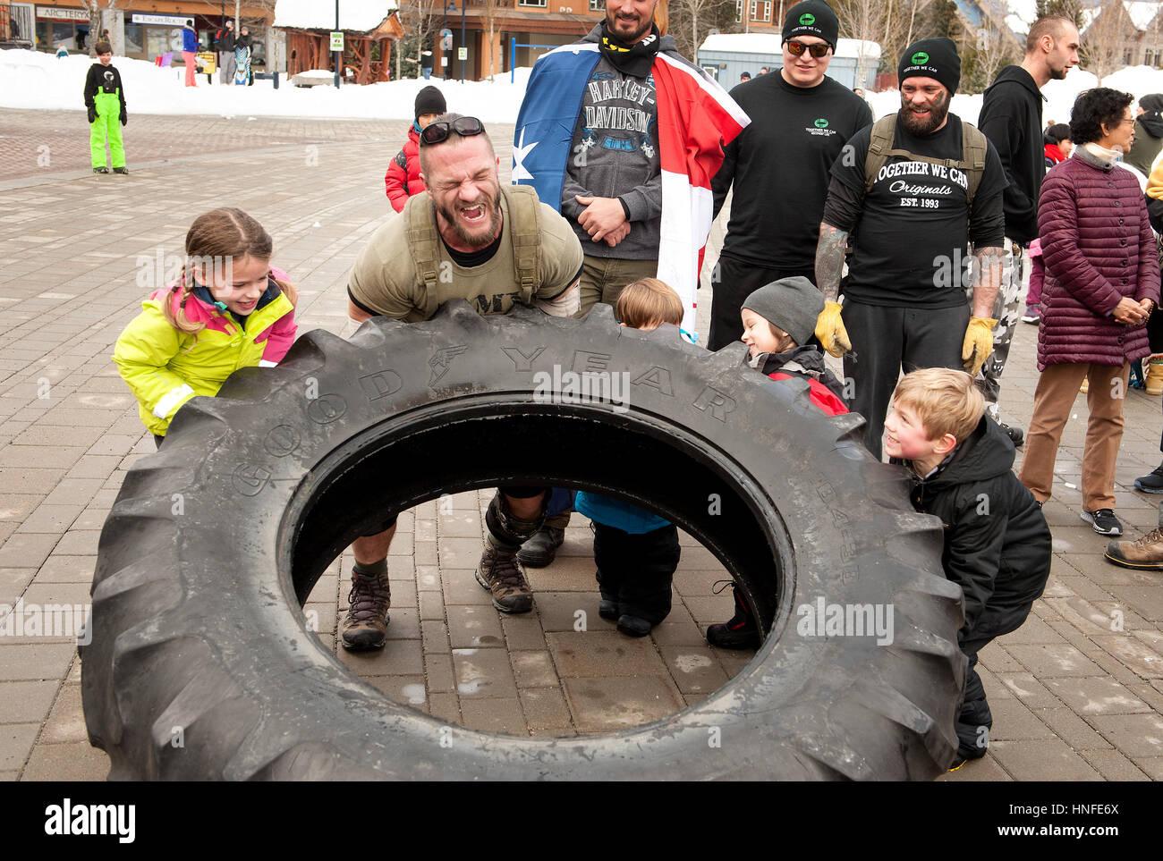 Terrance Joseph Kosikar flips a tire across the Whistler Olympic Plaza at the start of his 'It's Not Weak - Stock Image