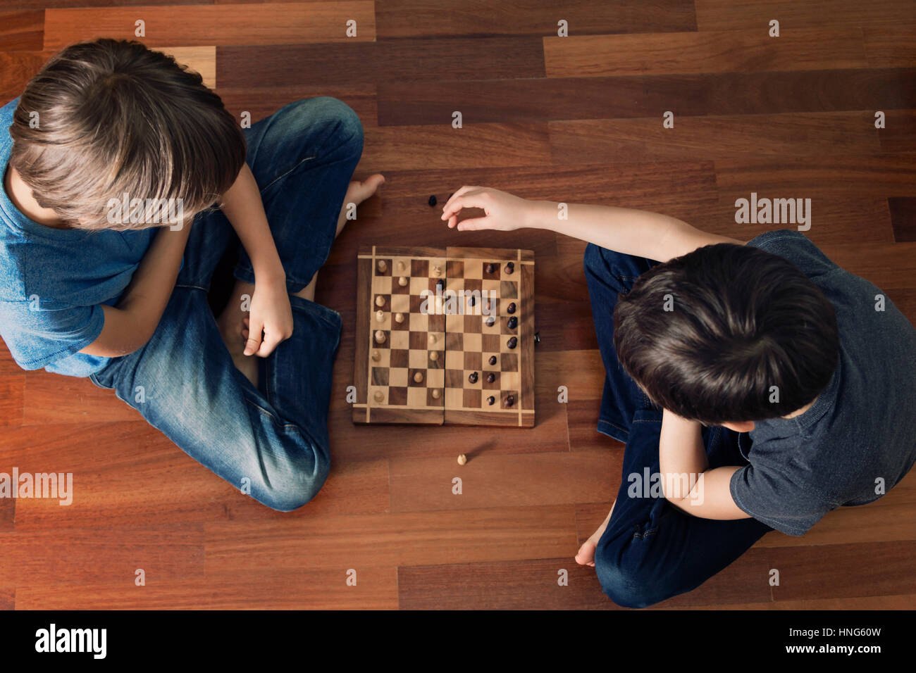 Kids playing chess sitting on wooden floor. Top view. Game, education, lifestyle, leisure concept. Toned image - Stock Image