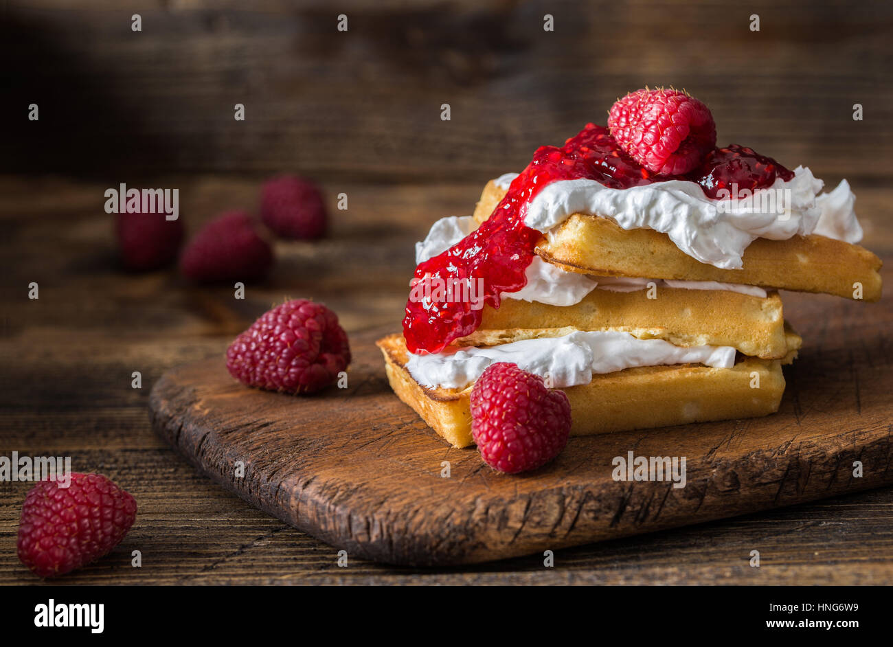 Belgian waffles with raspberries and double cream on rustic table. - Stock Image