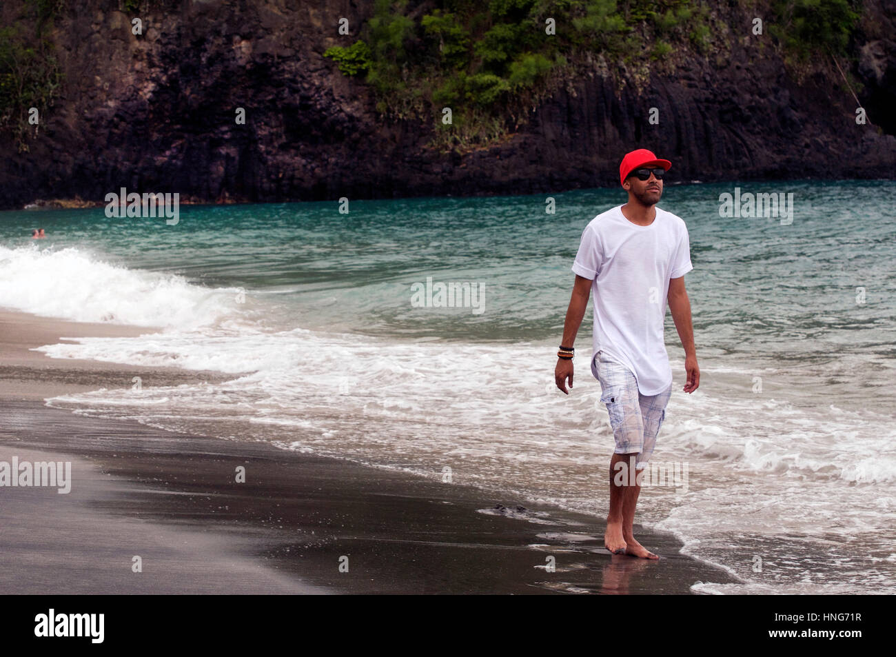 Cool Dude Strolls Along Sandy Beach in Bali Indonesia Wearing Red Baseball Hat, White T-Shirt and Short Pants Stock Photo
