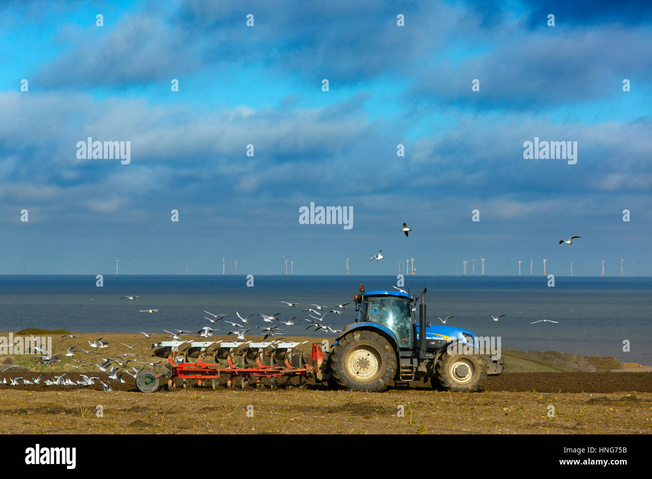 Spring Ploughing near Salthouse with Sheringham Shoal  wind farm in the background  Norfolk - Stock Image