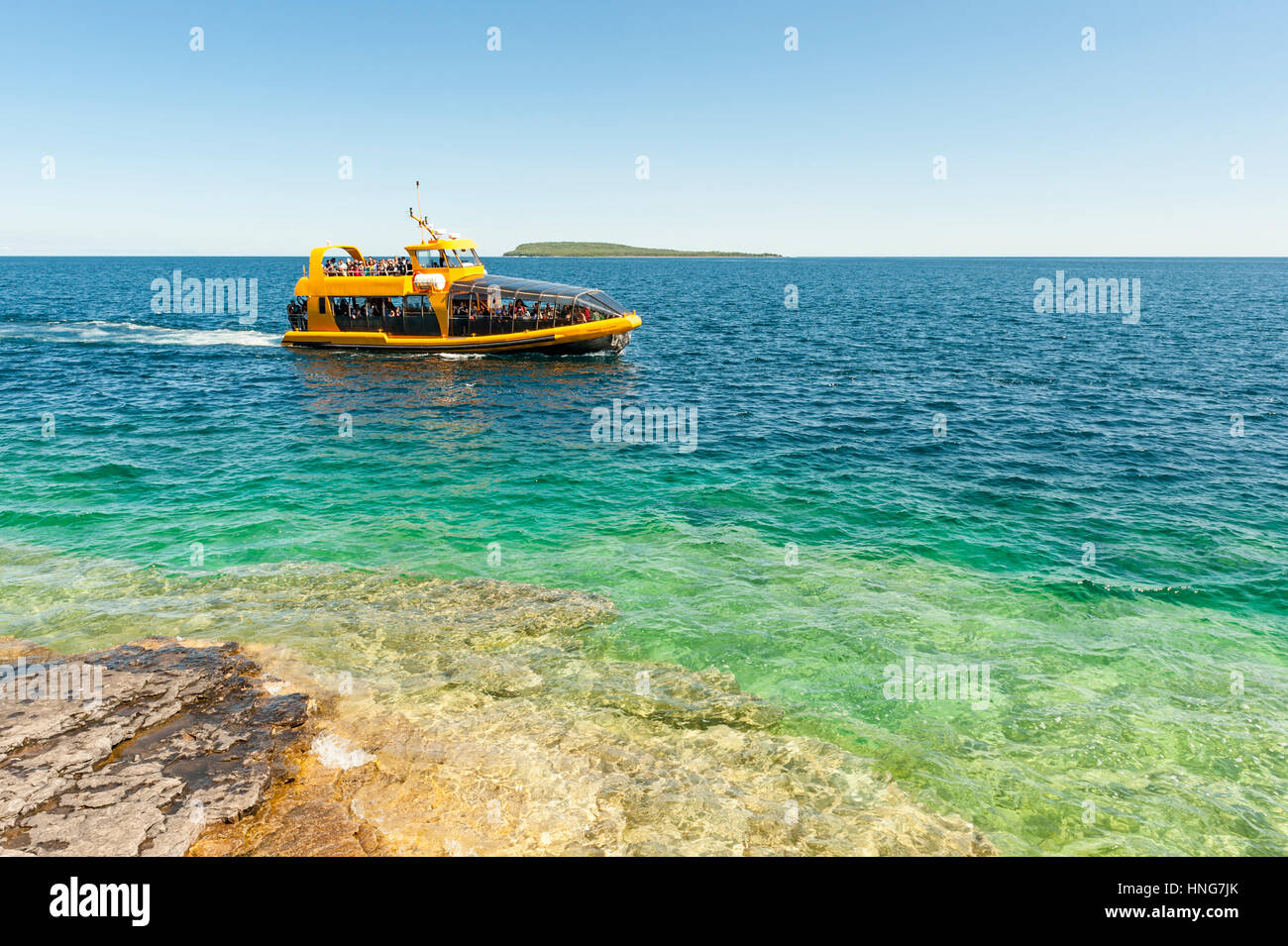 A tour boat passes by the shore of Flowerpot Island on Georgian Bay at Fathom Five National Marine Park, Bruce Peninsula, - Stock Image