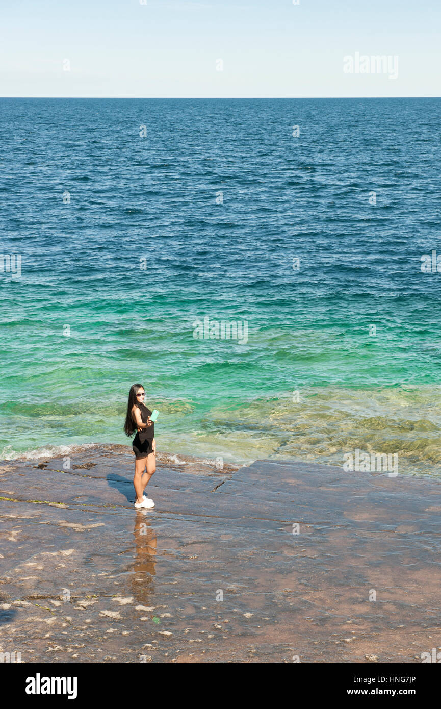 Female asian tourist taking a selfie with a smartphone by the edge of Lake Huron, Georgian Bay, Bruce Peninsula, - Stock Image