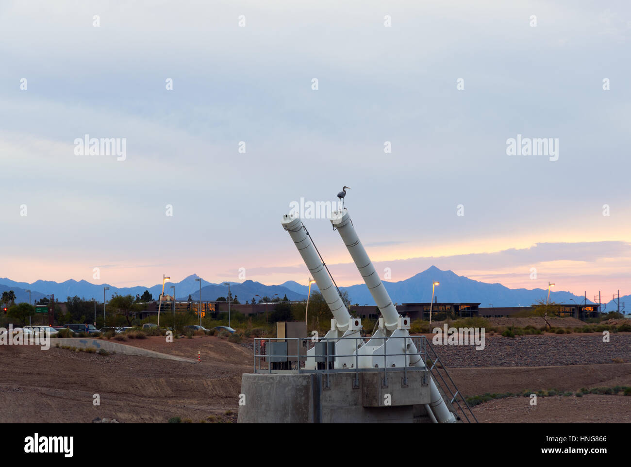 Tempe Town Lake Dam Hydraulic Cylinders With A Bird And Cloudy Sunset - Stock Image