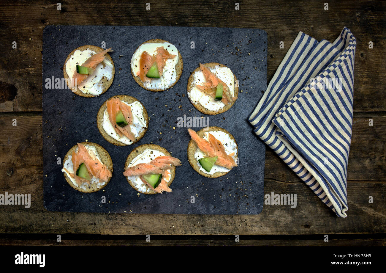 Oat Cake Cucumber and Salmon canapés on a black slate and rustic dark wood background with cracked black pepper - Stock Image