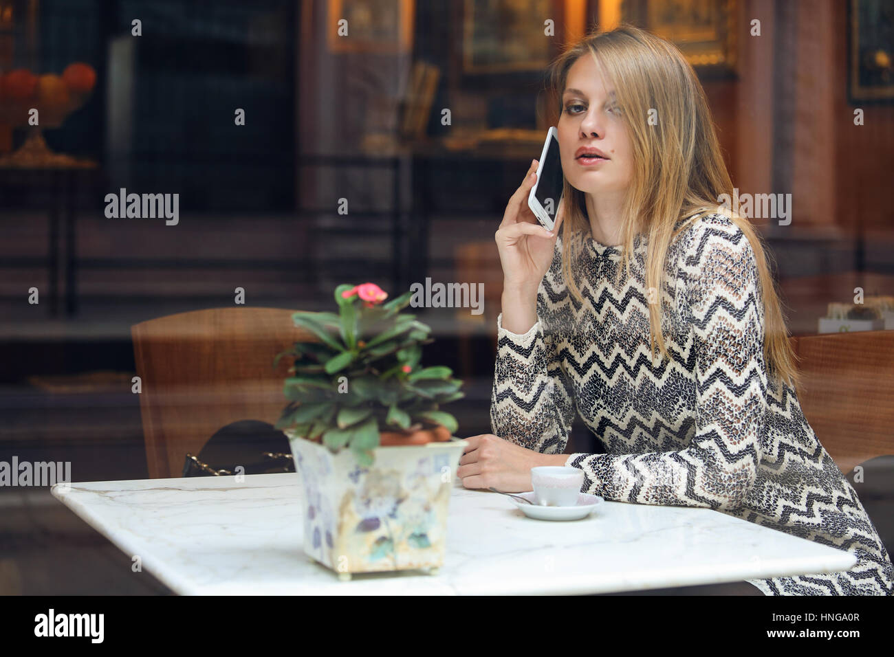 Beautiful woman calling with her smartphone. City cafe - Stock Image