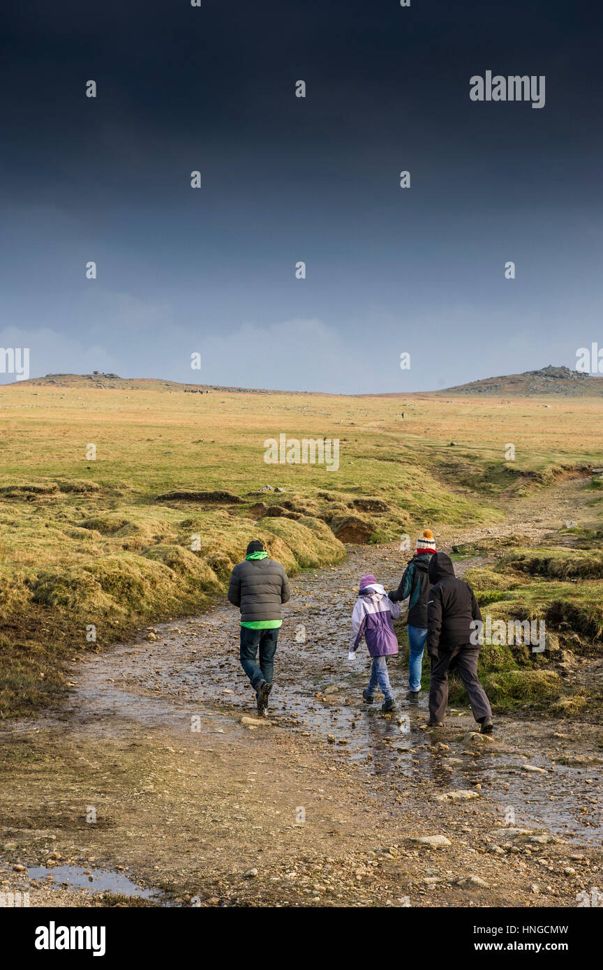 A family walking along a muddy footpath on Rough Tor, Bodmin Moor, Cornwall. - Stock Image