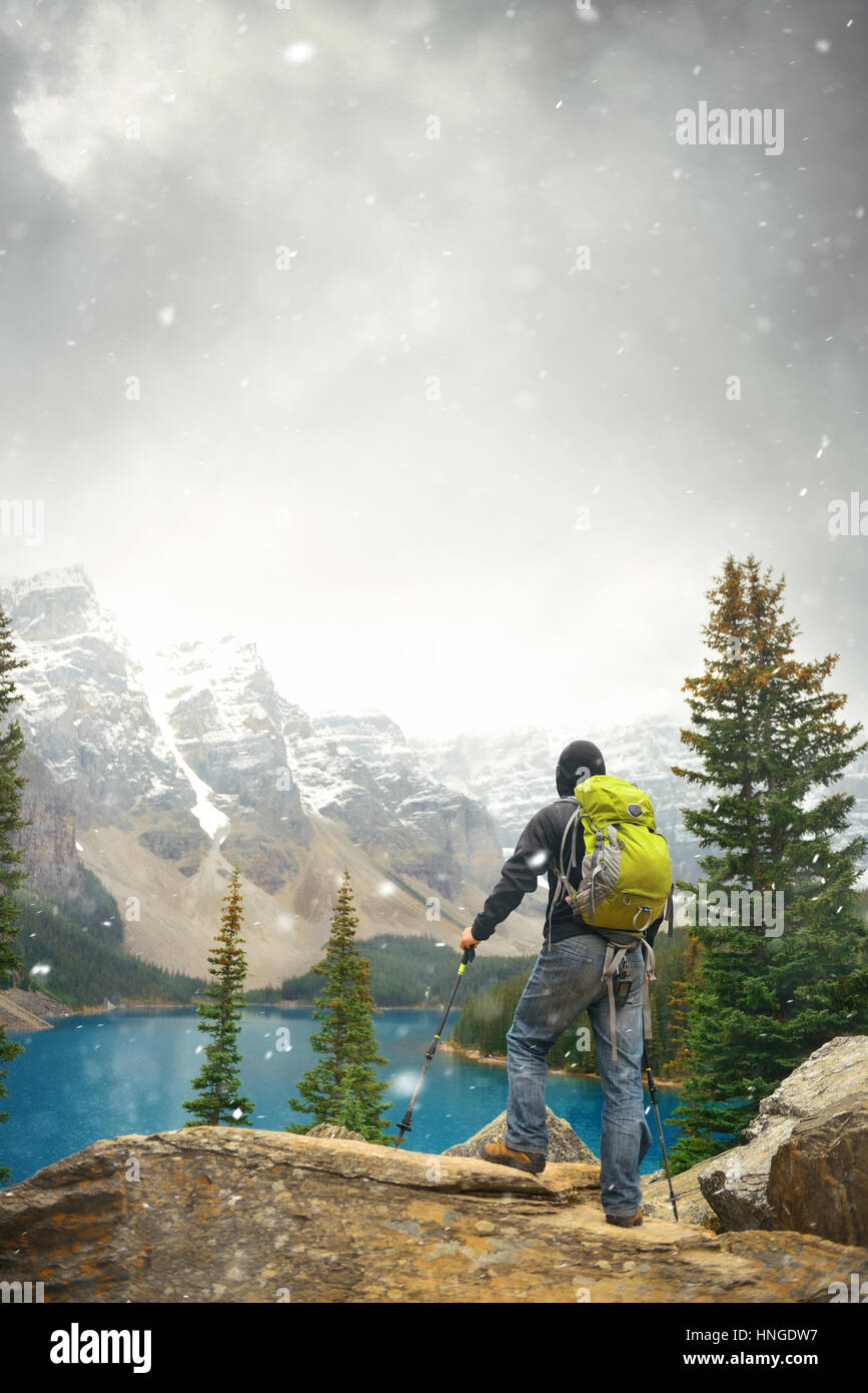 Hiker in Moraine Lake with snow capped mountain of Banff National Park in Canada in a snowing day Stock Photo