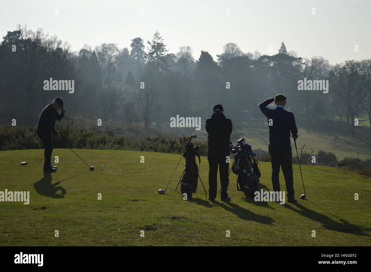 Three golfers teeing off at Reigate Hill Golf Club, Surrey, UK - Stock Image