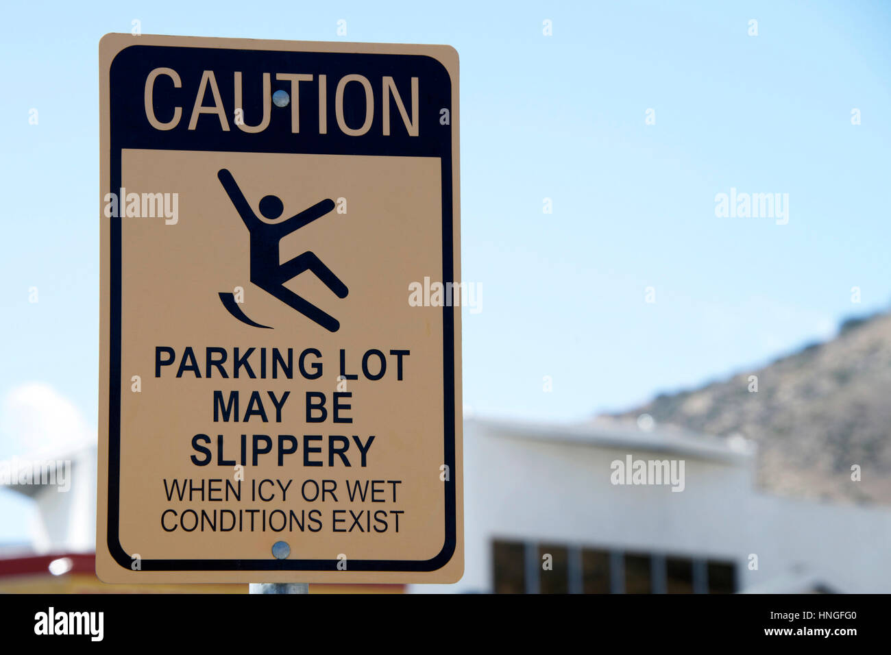 Caution, Slippery when wet sign in a parking lot. Warning patrons - Stock Image