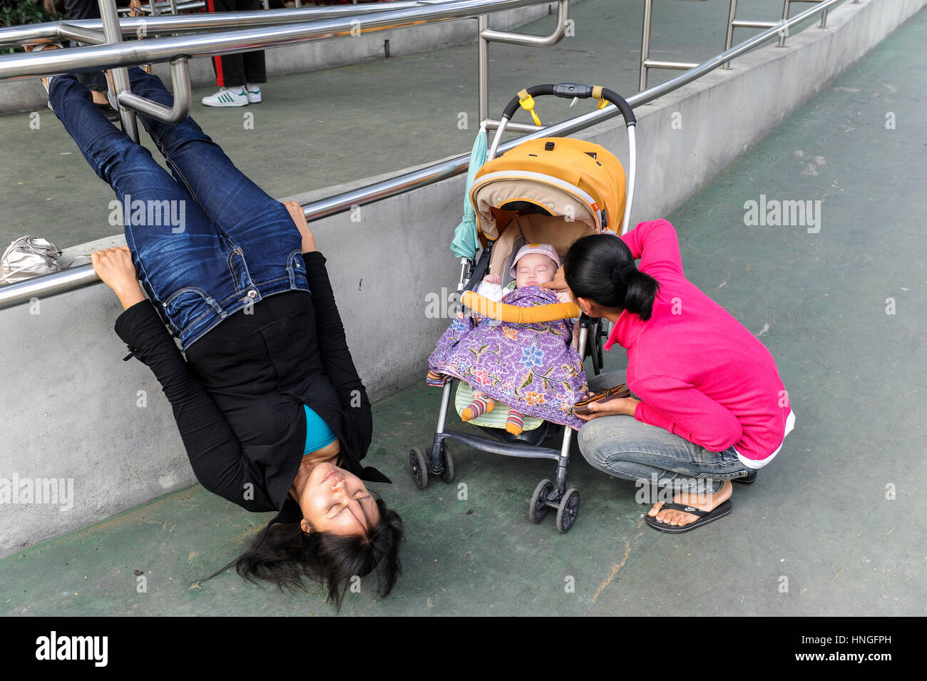 CHINA, Megacity Hong Kong, Kowloon, people doing exercise in public park, infant in baby chair wagon - Stock Image