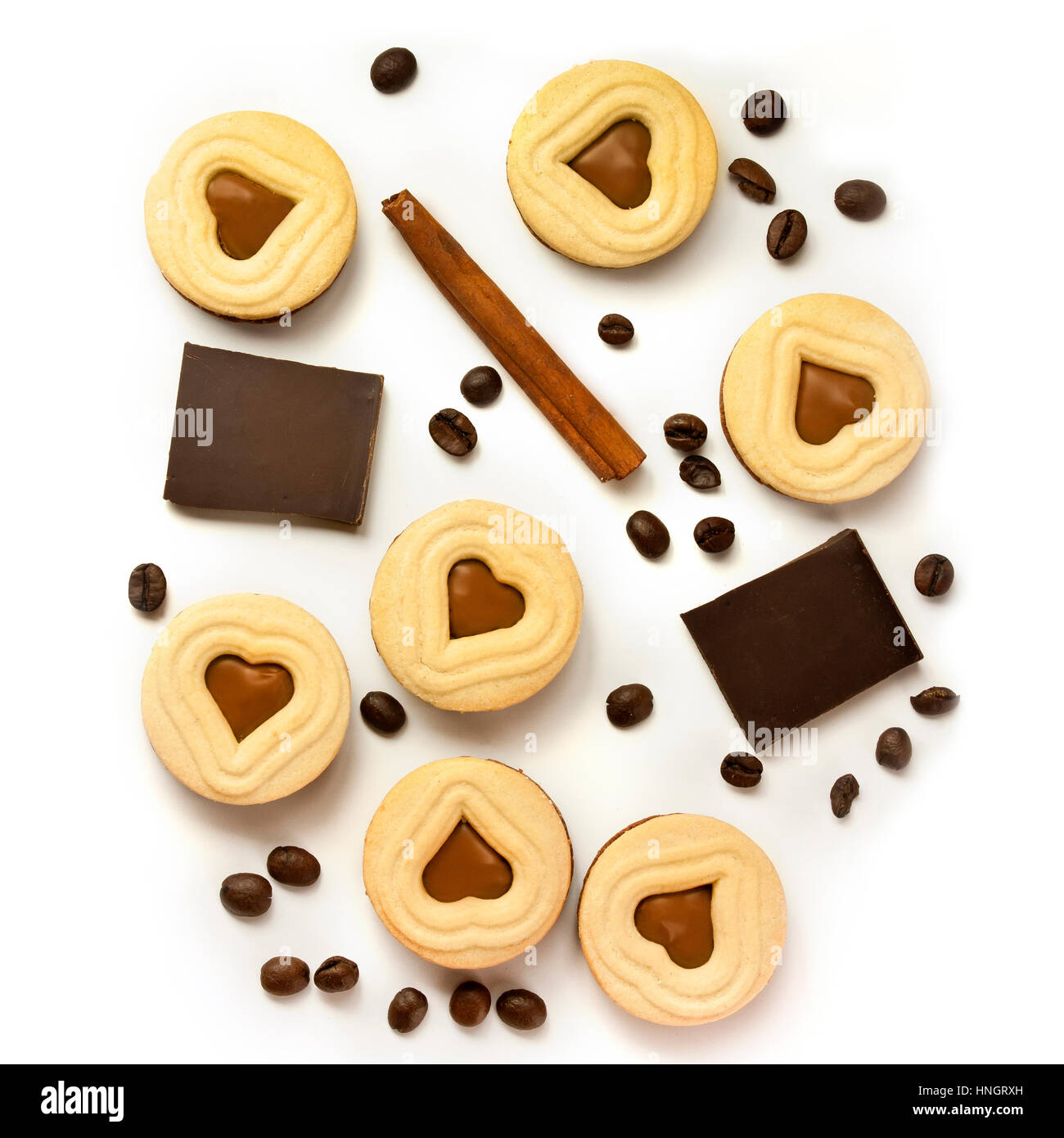 A square photo of pieces of chocolate, cocoa cookies with heart-shaped fillings, coffee beans and a cinnamon stick, - Stock Image