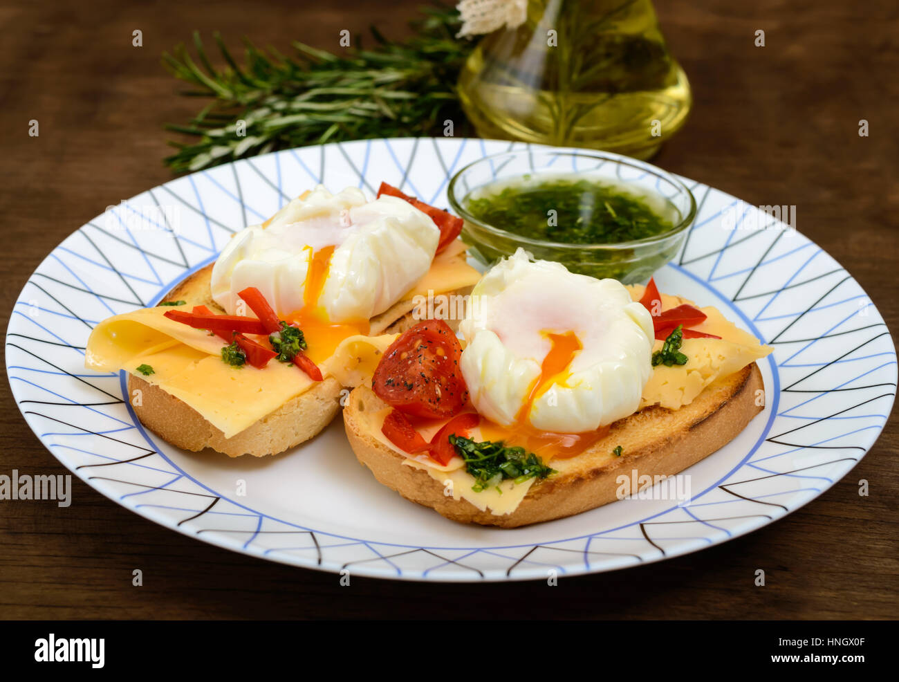 Crispy toast with poached egg, cheese, peppers, tomatoes, souse on a plate on a dark wooden background. Close up - Stock Image