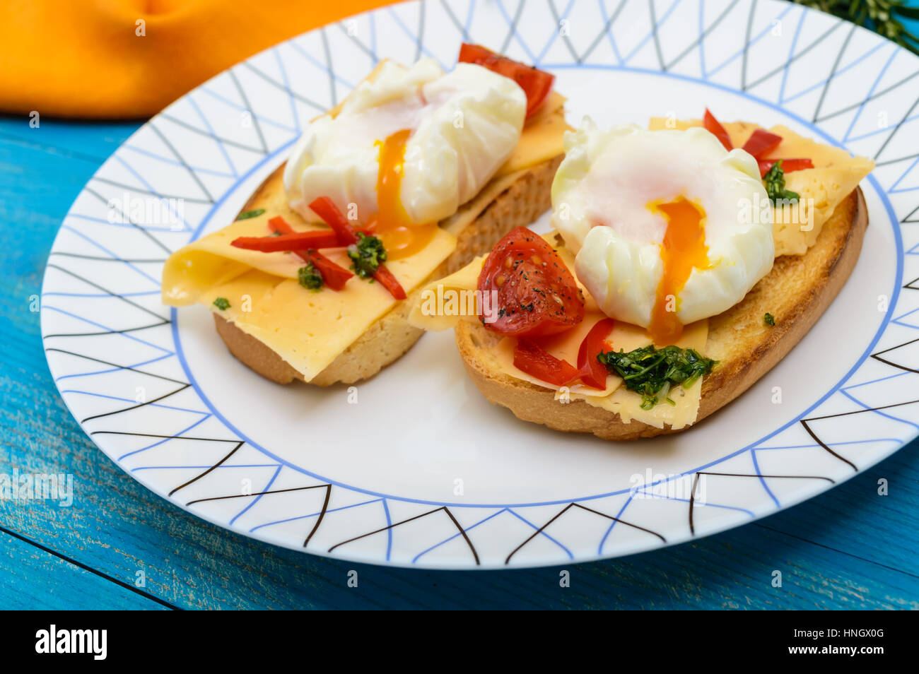 Crispy toast with poached egg, cheese, peppers, tomatoes, souse on a plate on a blue background. Close up - Stock Image