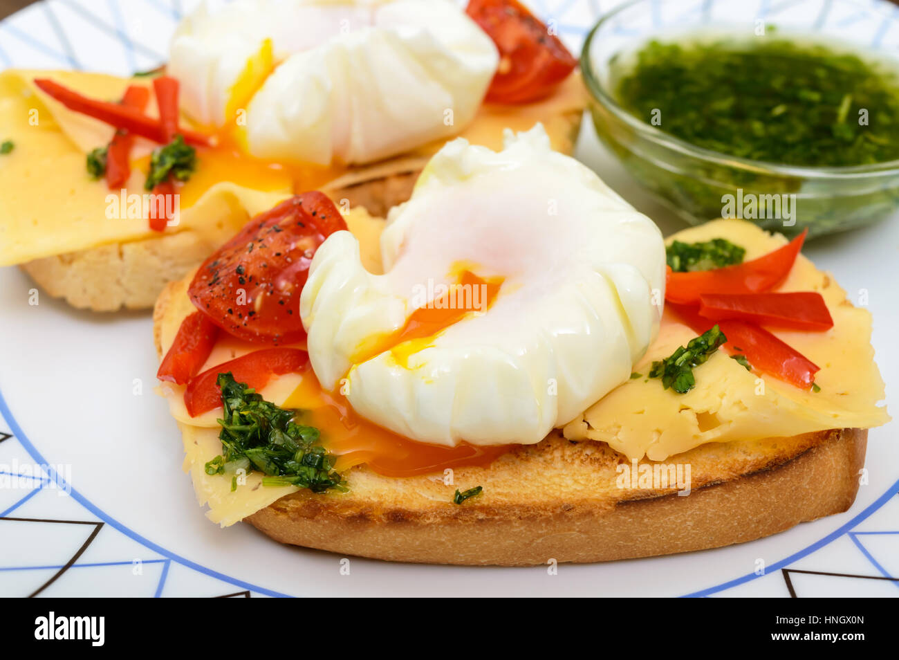 Crispy toast with poached egg, cheese, peppers, tomatoes, souse on a plate. Close up - Stock Image