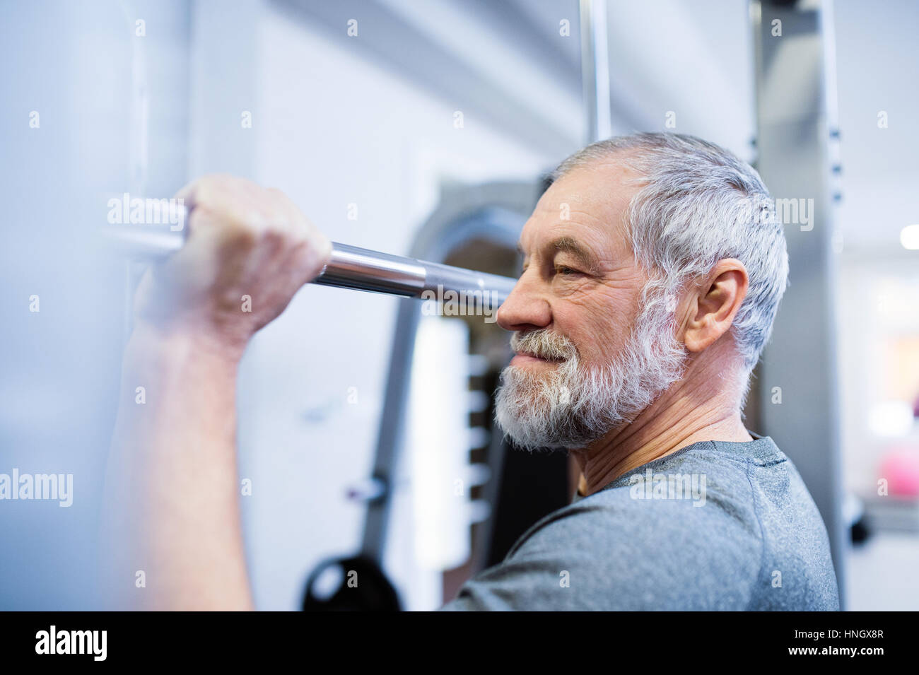 Senior man in gym doing pull-ups on horizontal bar. - Stock Image