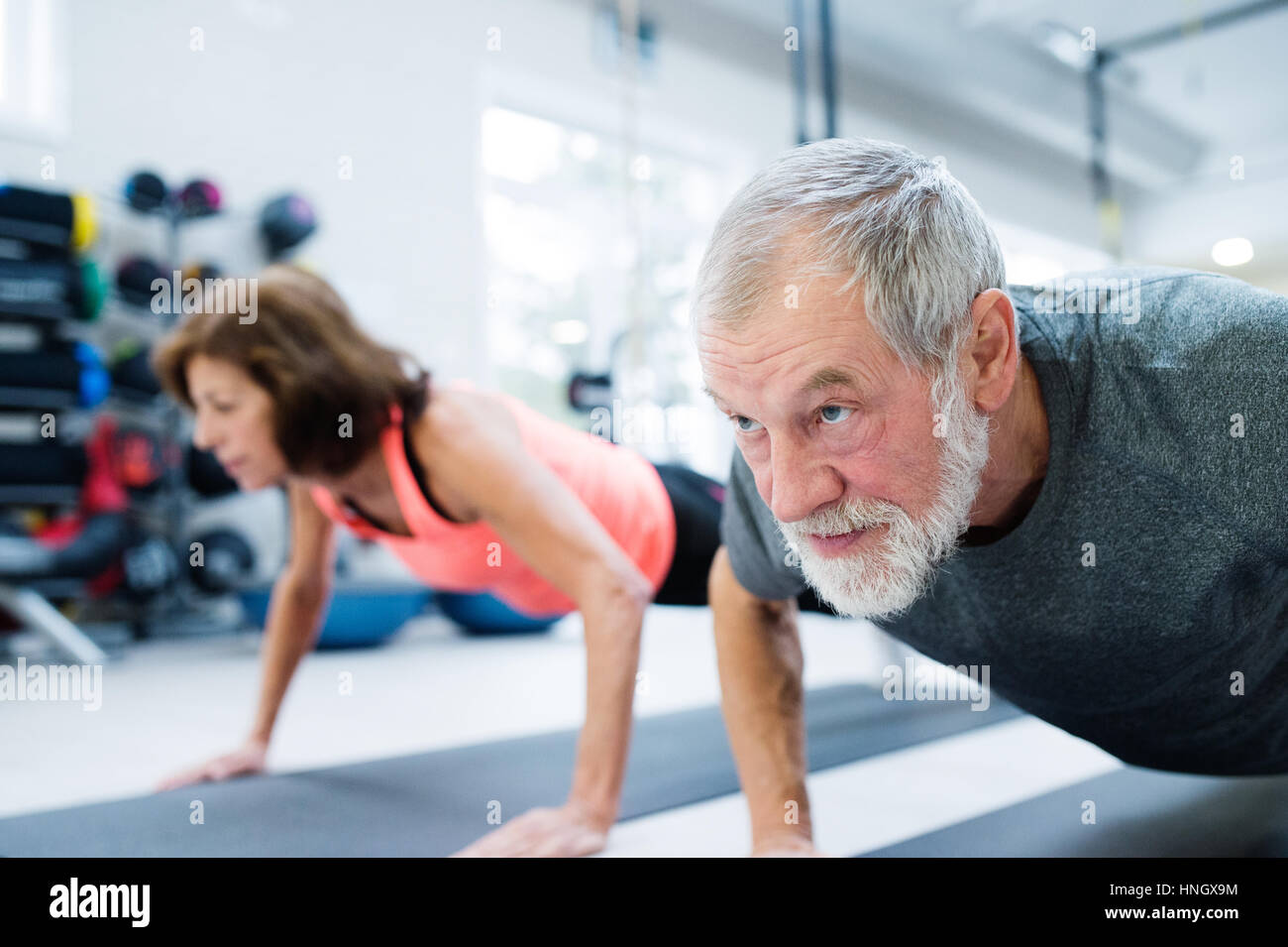 Senior couple in gym working out, doing push ups - Stock Image