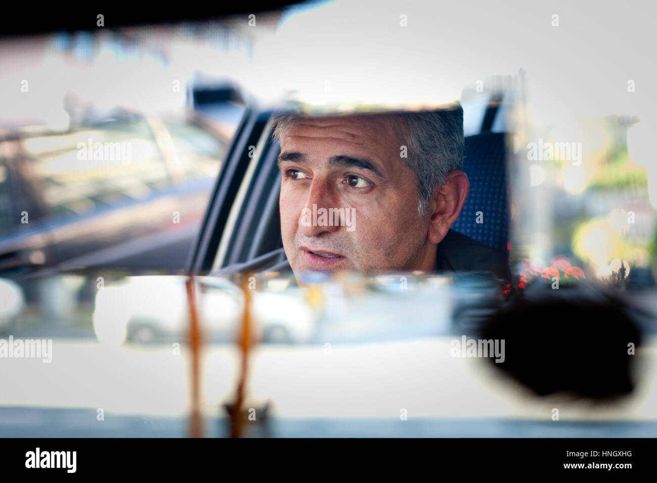 Istanbul, Turkey - November, 7 2009: Man's face reflected in rear view mirror as he drives a taxi through the - Stock Image