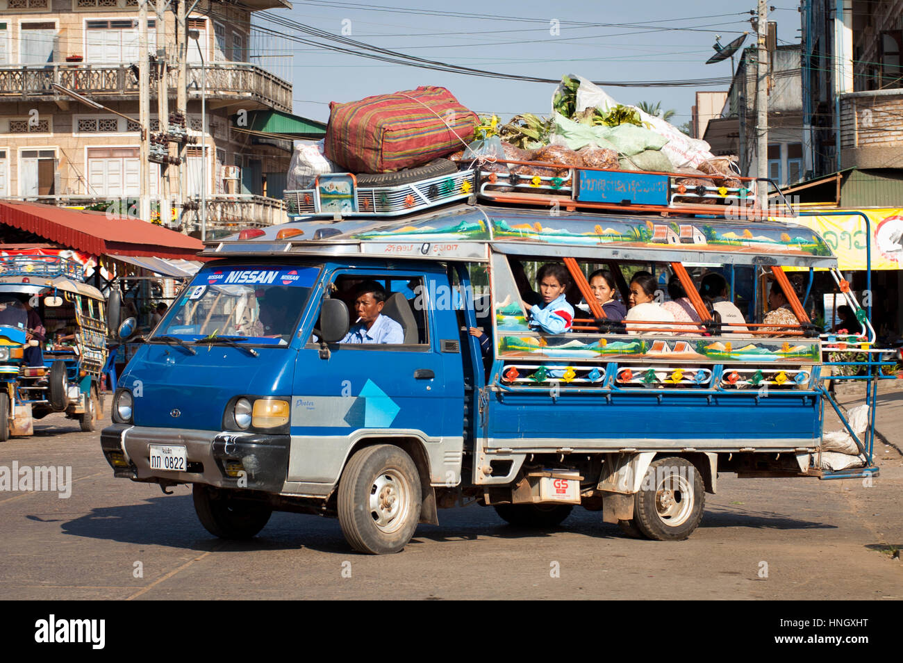 Pakse, Laos - January, 13 2005: A packed Songthaew minibus drives through the town of Pak Se in Laos. A Songthaew - Stock Image