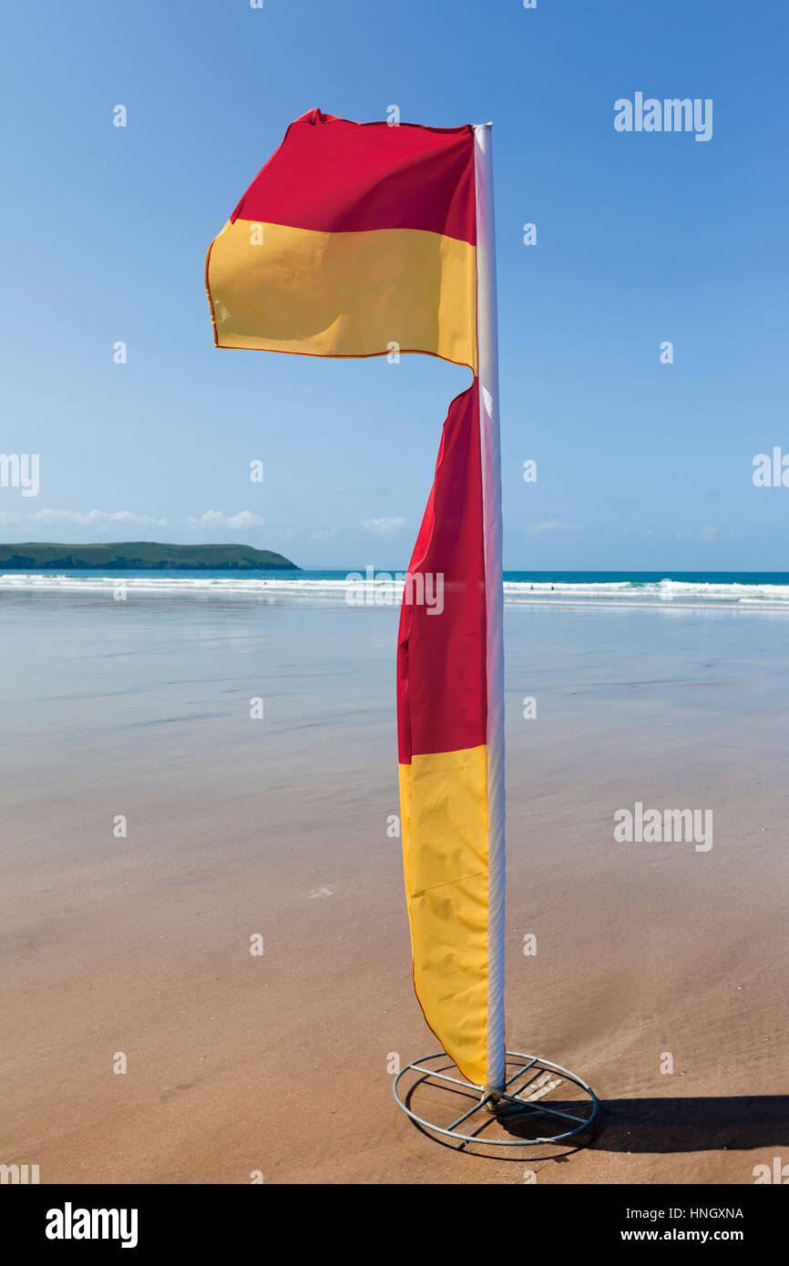 WOOLACOMBE, UK - MAY 19: Red and yellow safety flag fluttering in the wind on Woolacombe beach in North Devon on - Stock Image