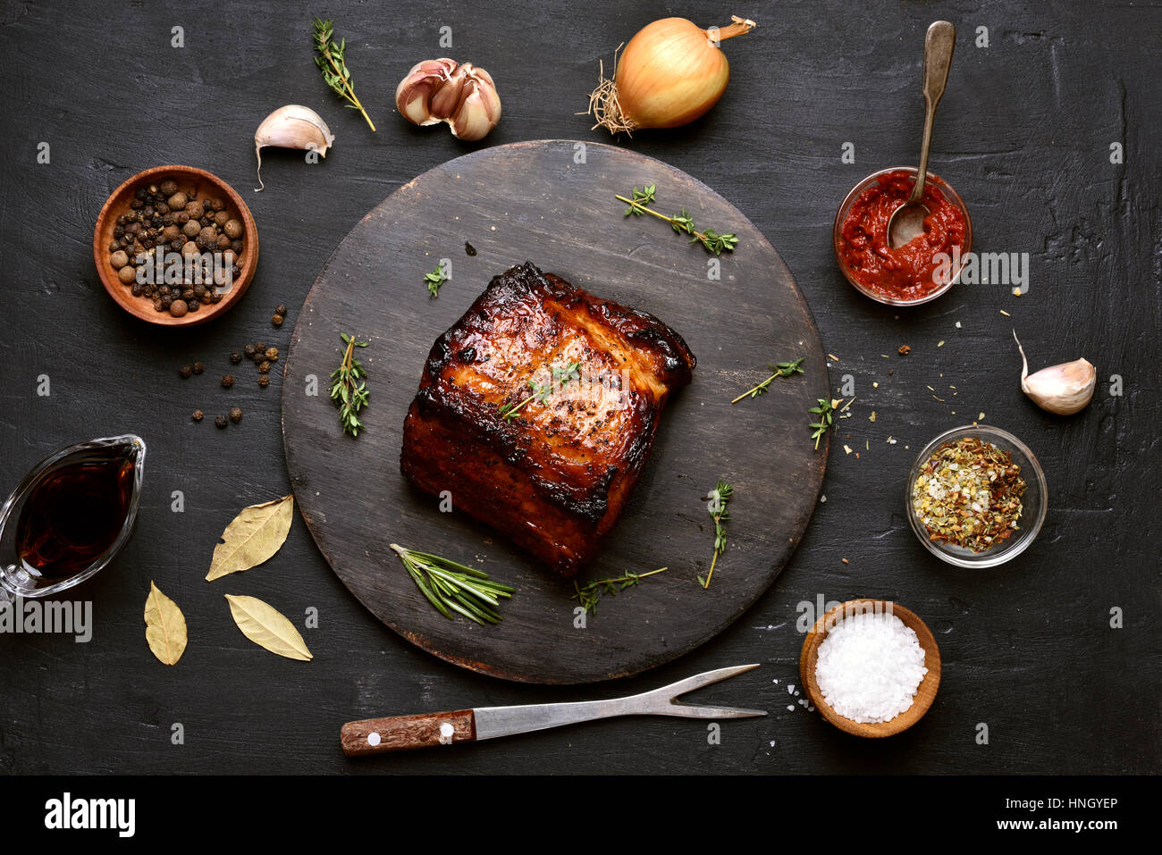 Grilled meat and ingredients on dark background, top view - Stock Image