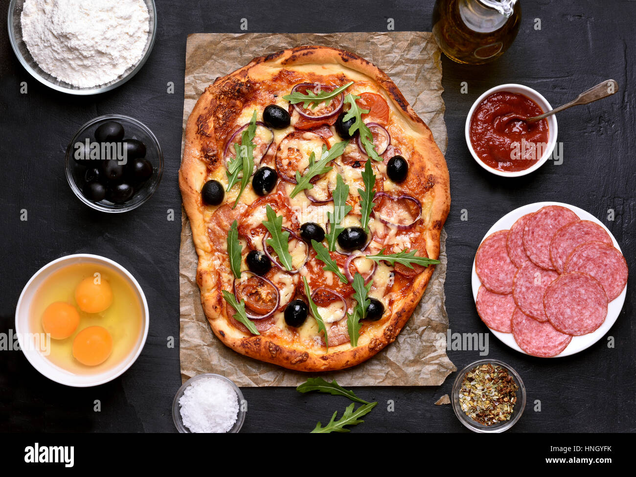 Homemade pizza and ingredients on dark background, top view - Stock Image