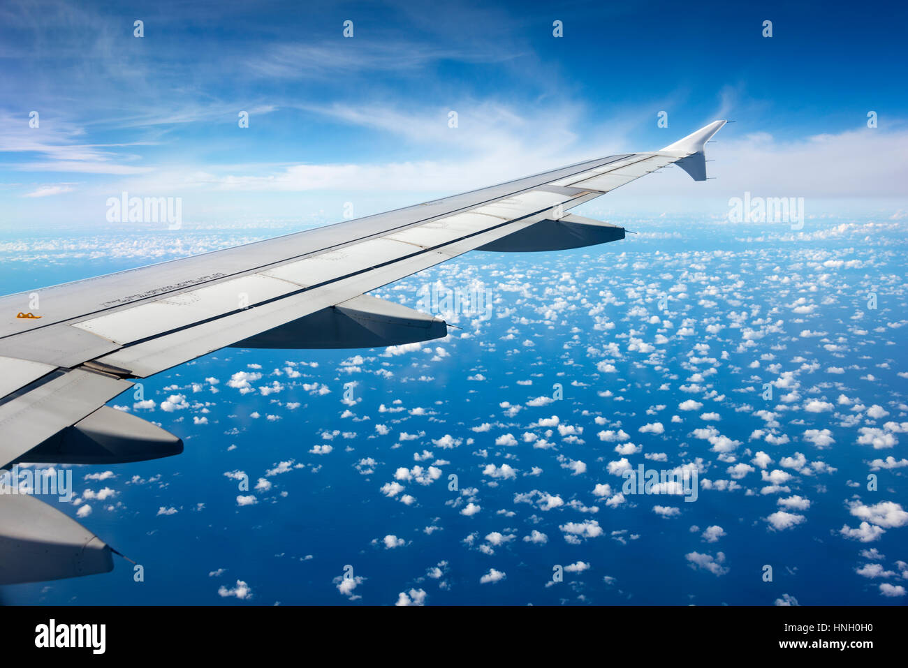 Airplane wing above clouds - Stock Image