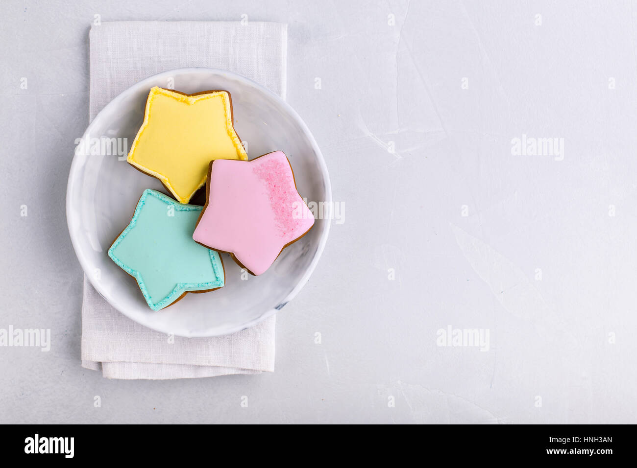 Star shaped cookies in three various colors on plate shot from above - Stock Image