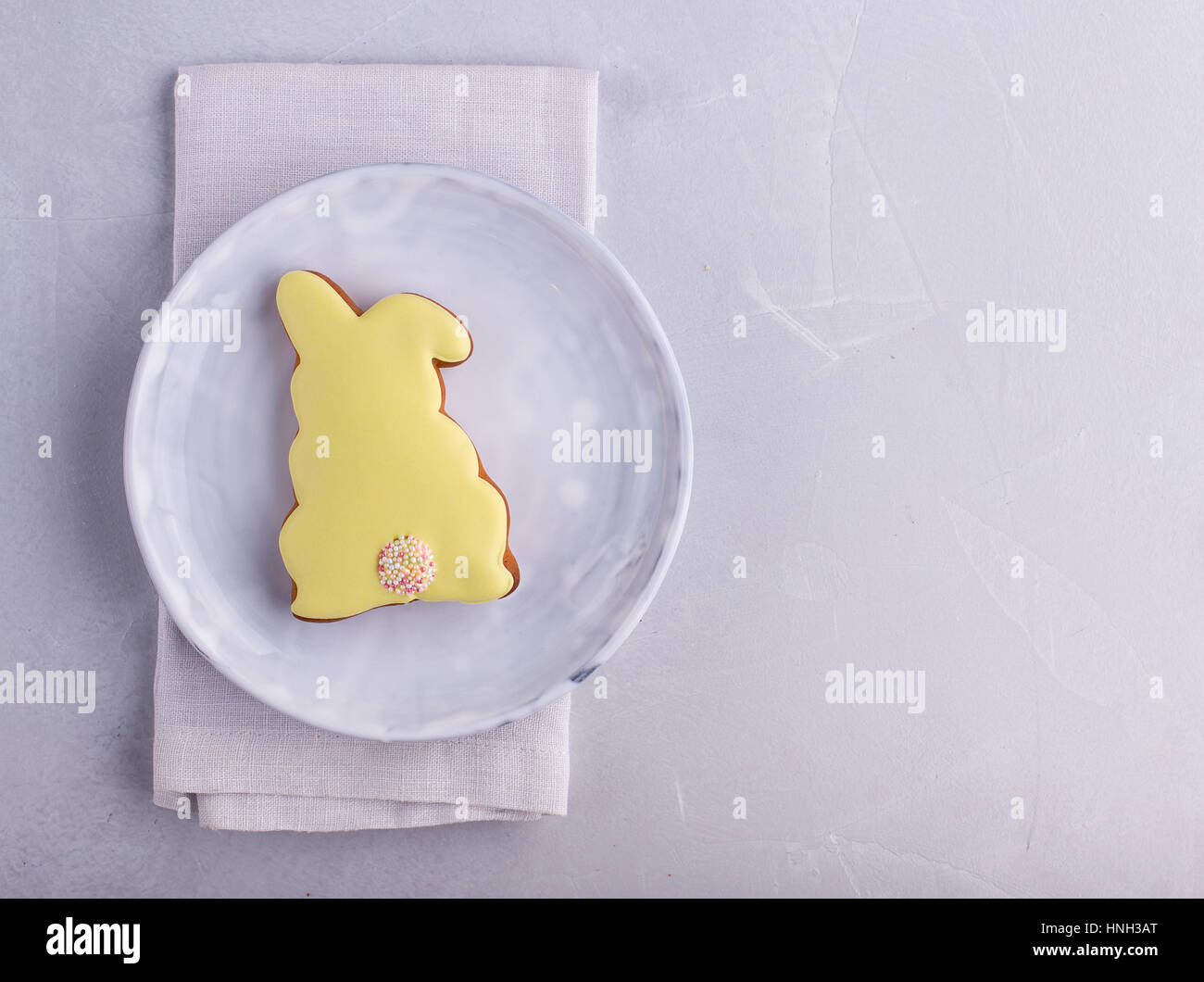 Easter rabbit cookie on a light grey plate with copyspace - Stock Image