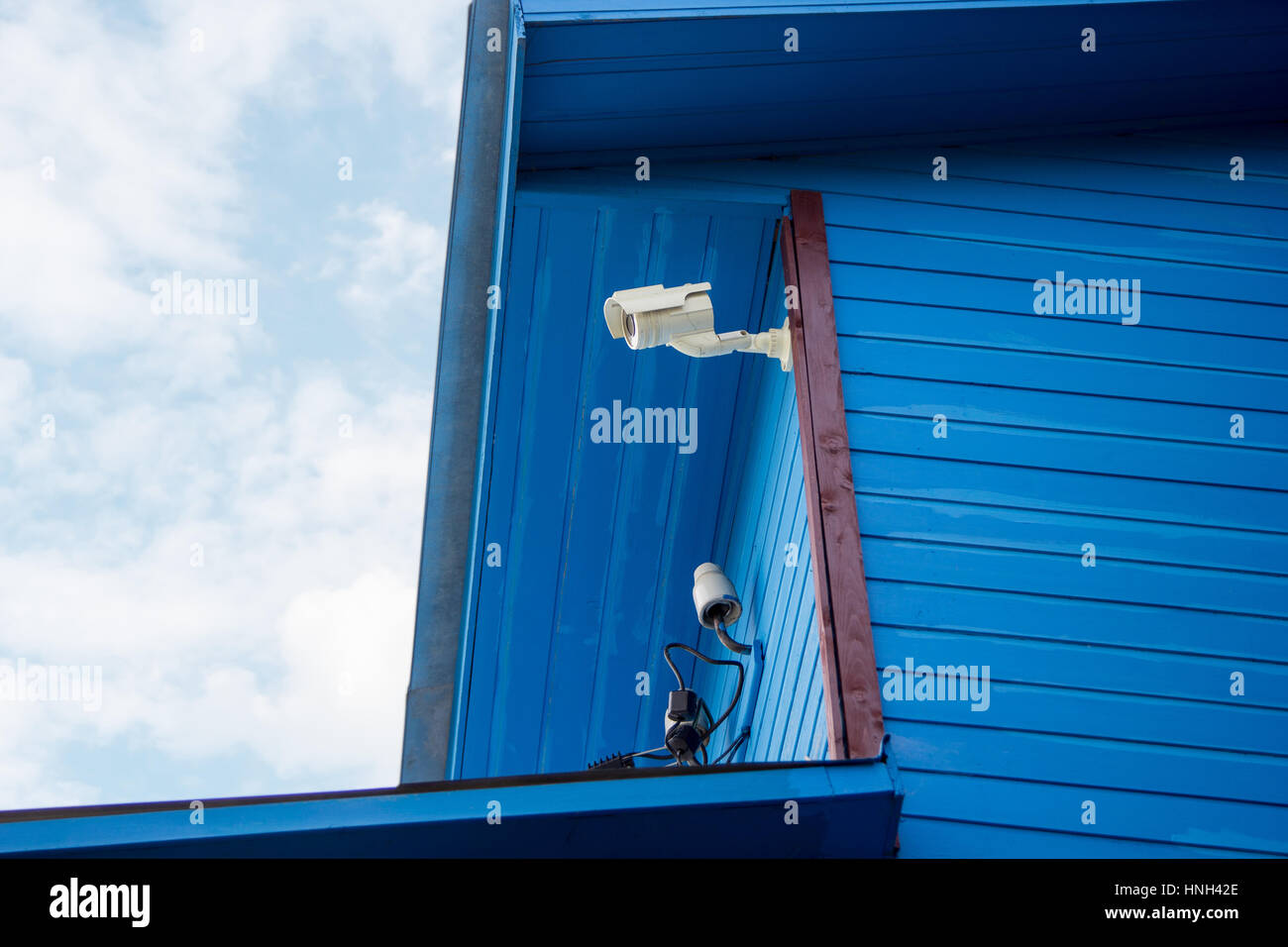 Surveillance camera on the wall of a wooden house - Stock Image