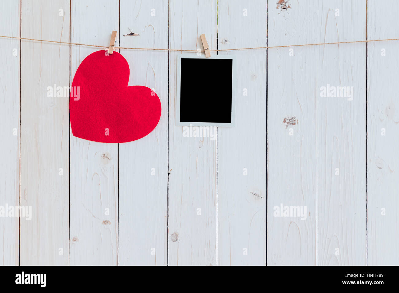 Red heart and photo frame blank hanging at clothesline on wood white ...