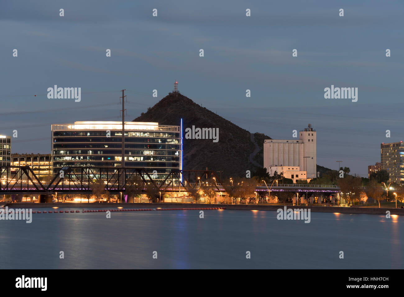 Downtown Tempe With Hayden Flour Mills, A Mountain, And Tempe Town Lake At Night - Stock Image