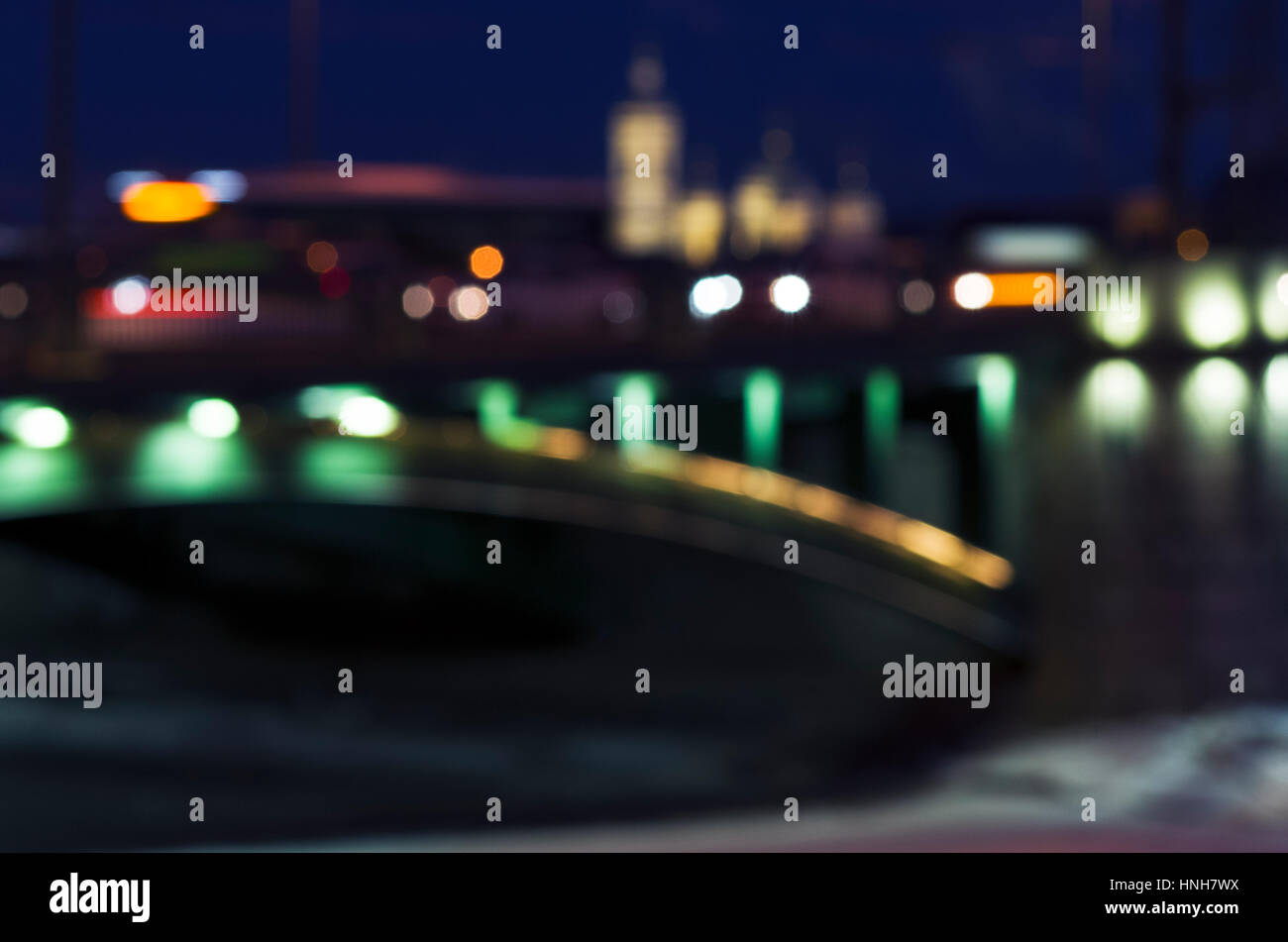 Unfocused photo of the cityscape with silhouettes of buildings, bridge, embankment and bus, Saint-Petersburg, Russia - Stock Image