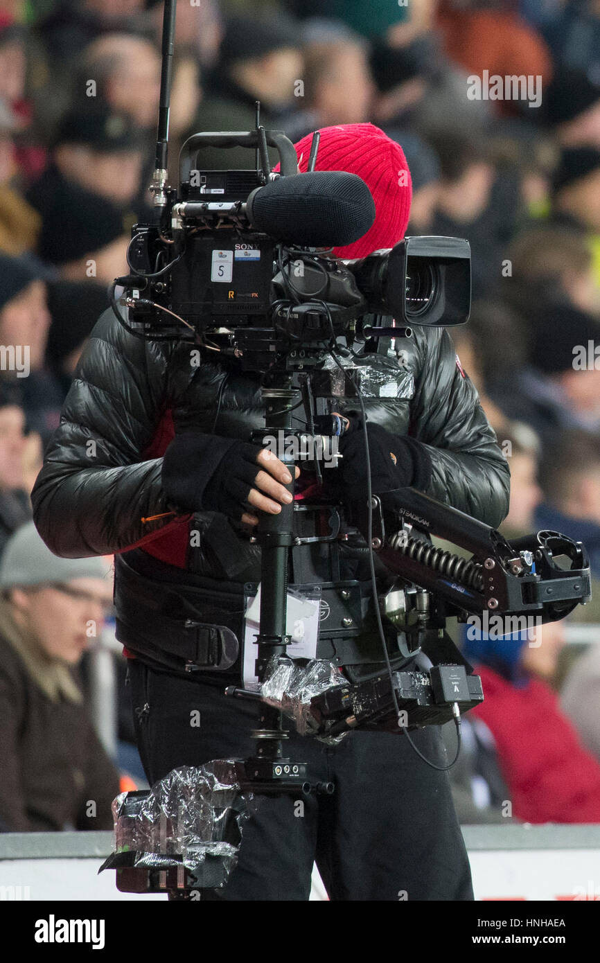 A TV cameraman uses a steadycam at a sporting event. - Stock Image