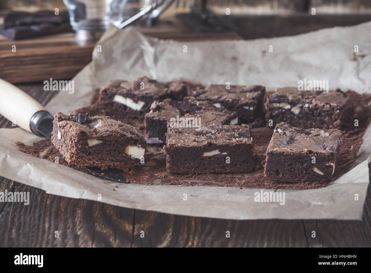 Homemade dark chocolate brownies with cream cheese on baking paper on rustic wooden table - Stock Image