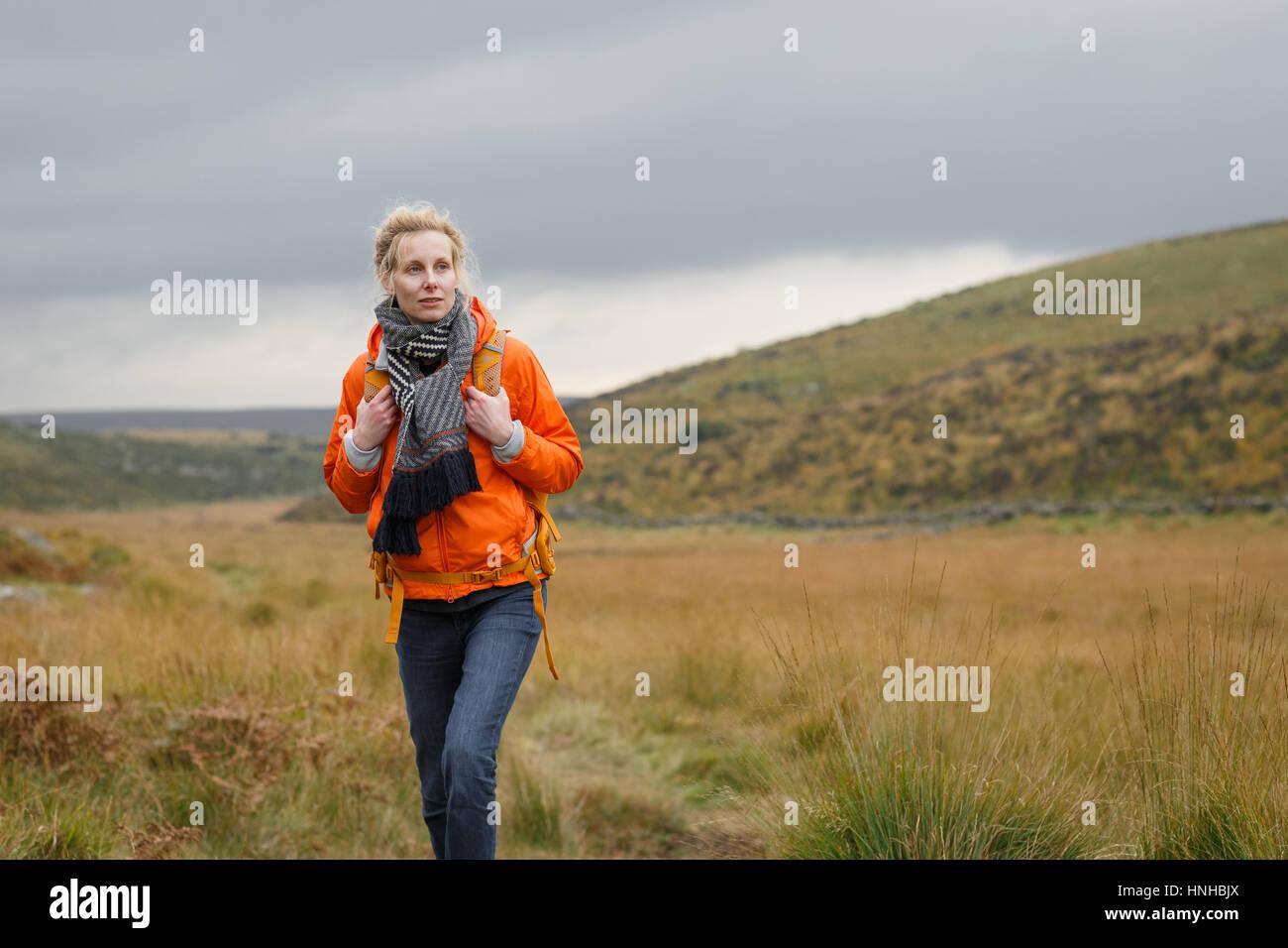 A woman hiking through Dartmoor National Park - Stock Image