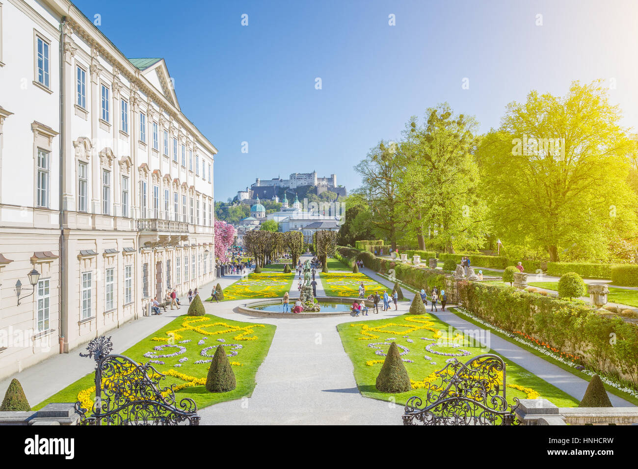 Classic view of Mirabell Gardens with famous Hohensalzburg Fortress in the background on a sunny day with blue sky - Stock Image