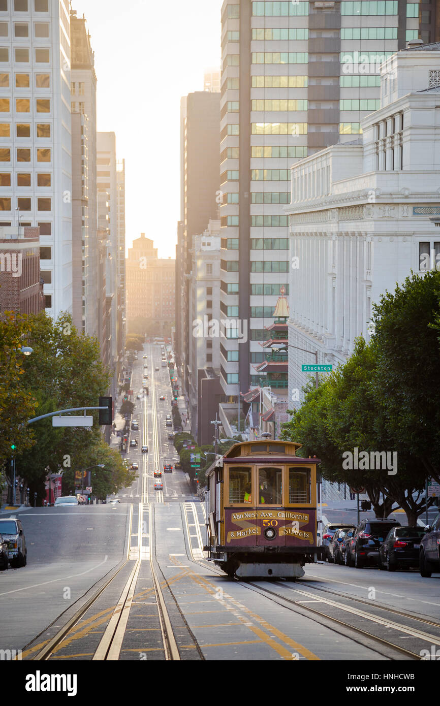 Classic view of historic Cable Car riding on famous California Street in beautiful golden morning light at sunrise - Stock Image