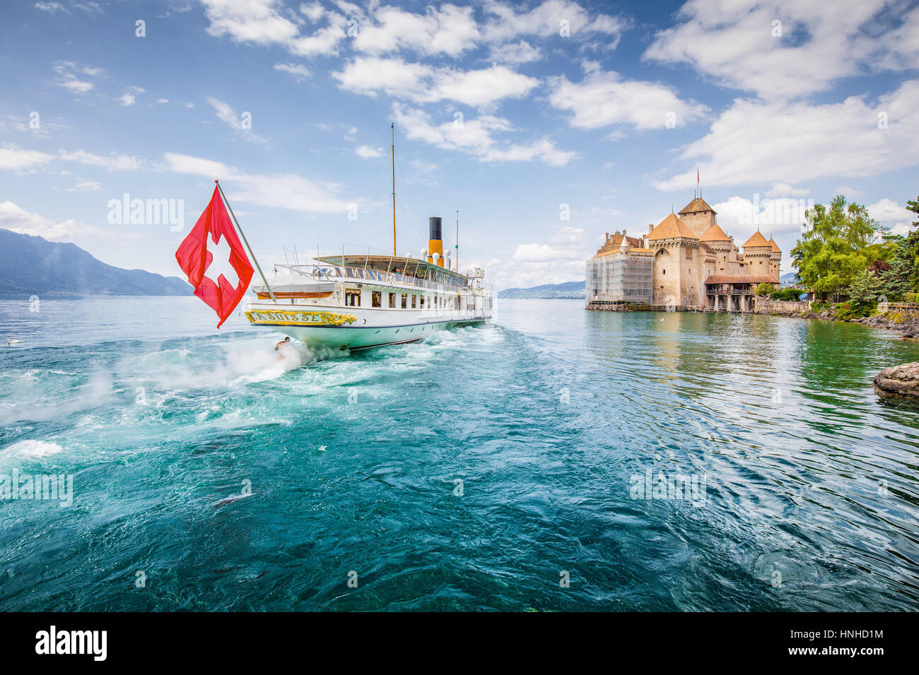 Traditional paddle steamer excursion ship with historic Chateau de Chillon at famous Lake Geneva on a sunny day - Stock Image