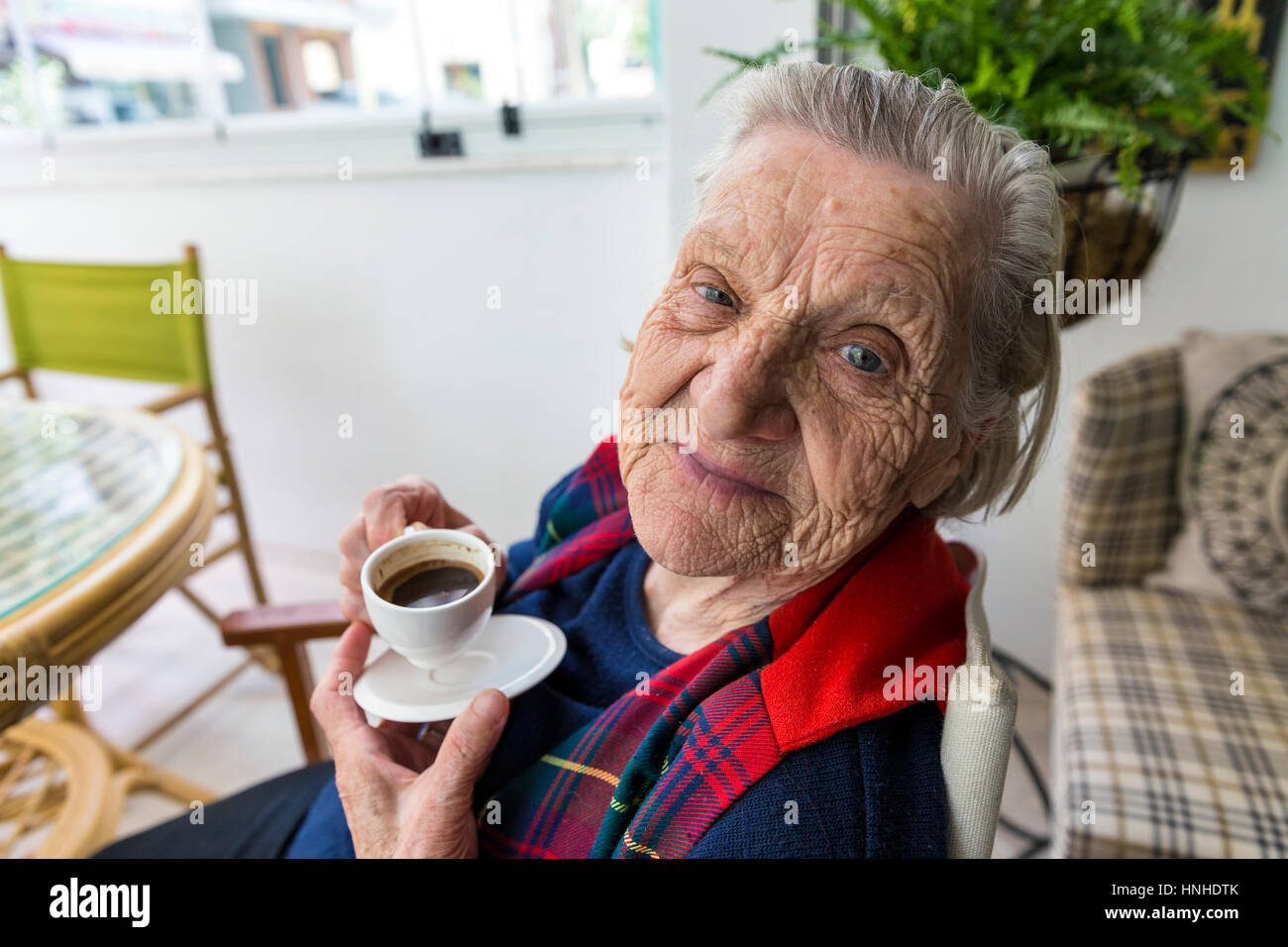 Senior old Turkish woman smiling to the camera and drinking Turkish coffee - Stock Image