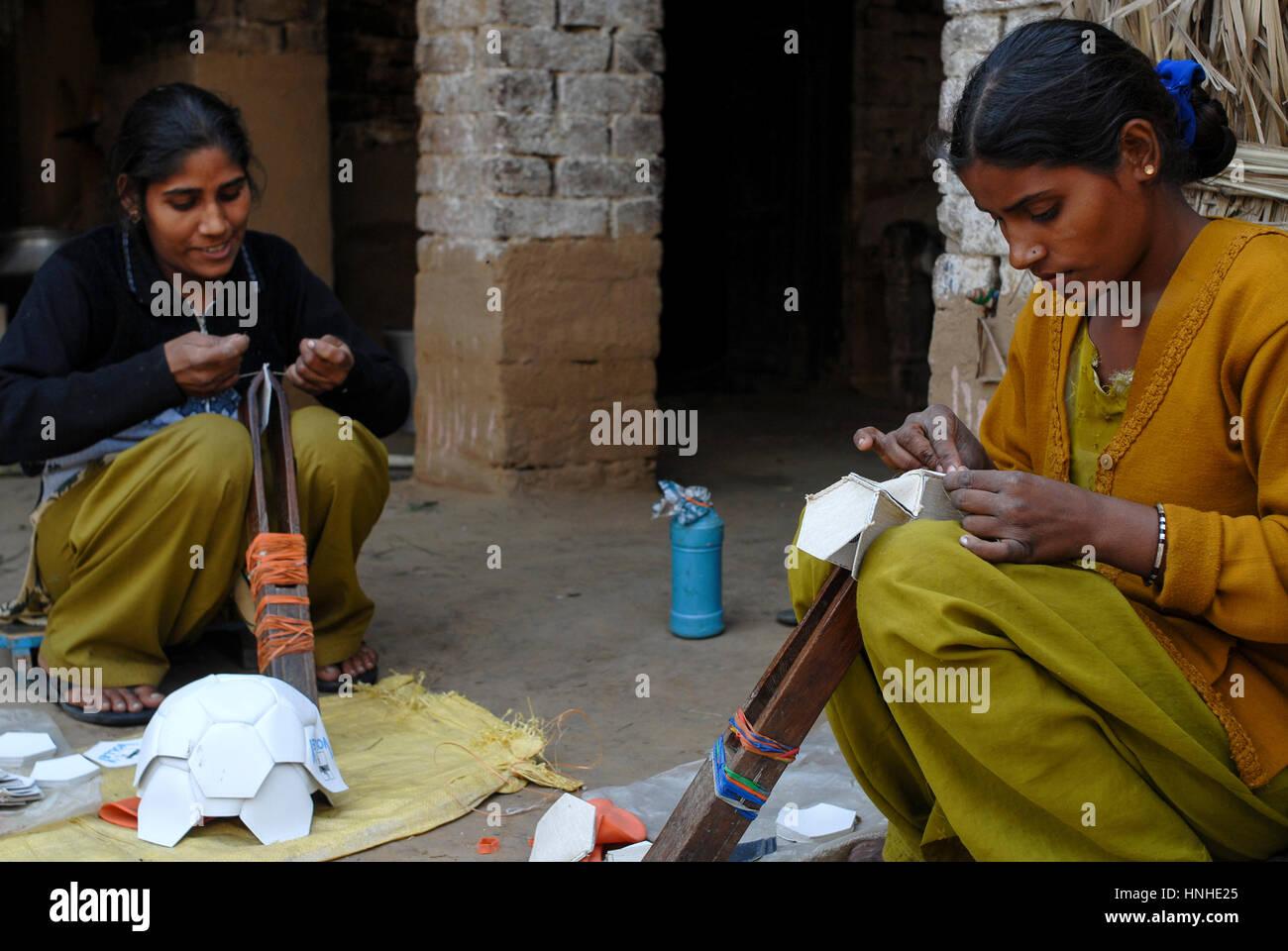 INDIA Uttar Pradesh, Meerut , village Kurali, cottage industry, dalit women stitch football - Stock Image