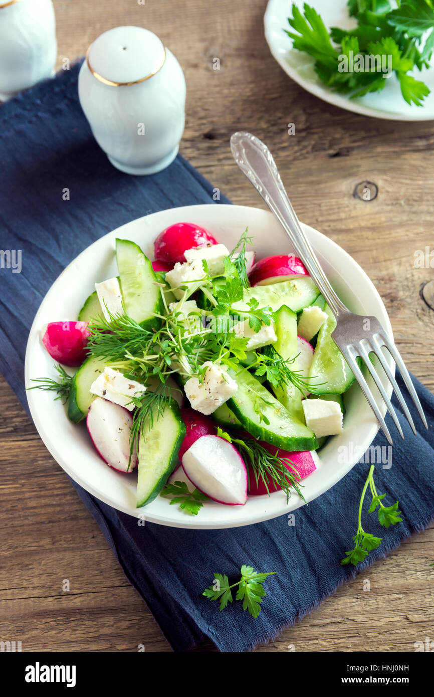 Spring salad with fresh cucumber, radishes, feta cheese, herbs, sprouts in bowl on wooden background - healthy detox - Stock Image
