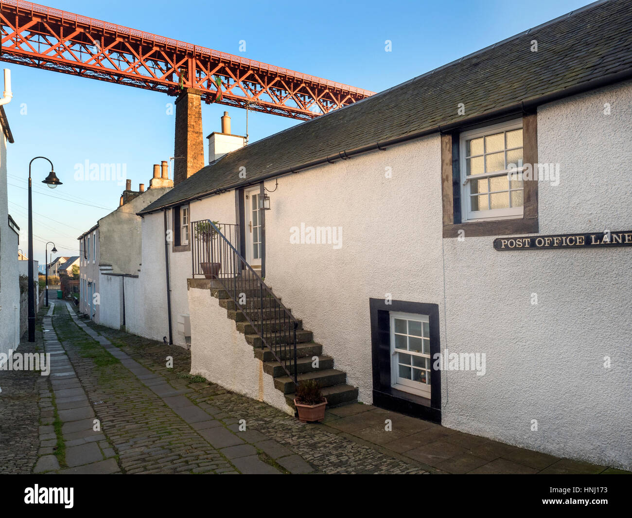The Forth Bridge Looms Over a Quiet Lane at North Queensferry Fife Scotland - Stock Image