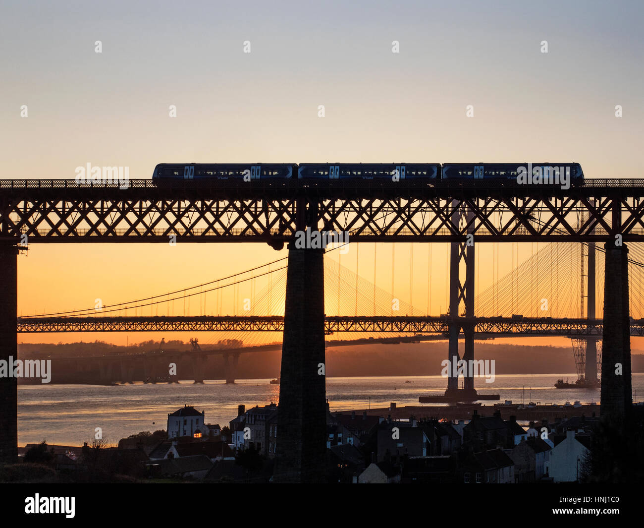 Passenger Train Crossing the Forth Bridge with the Road Bridges Behind at Sunset North Queensferry Fife Scotland - Stock Image