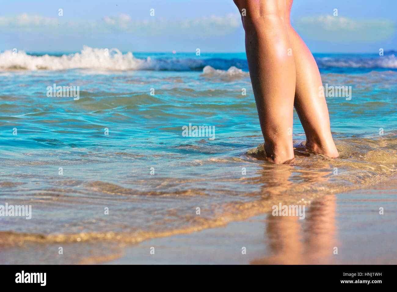 Girl standing with her feet in the water at 7 mile beach in Jamaica - Stock Image