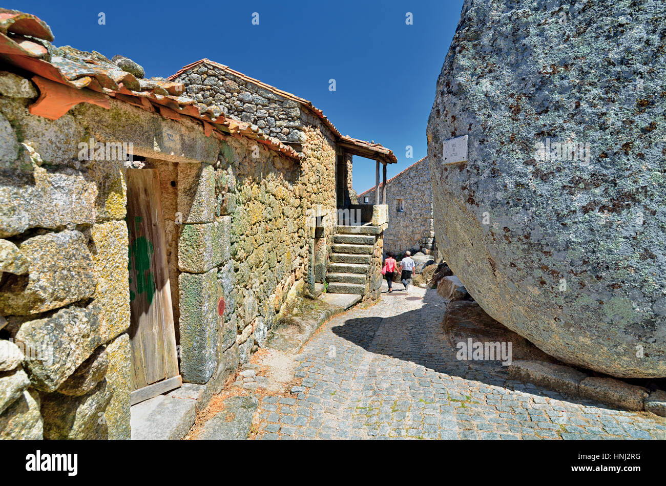 Portugal: Small alley passing granite stone houses and huge rocks in Monsanto - Stock Image