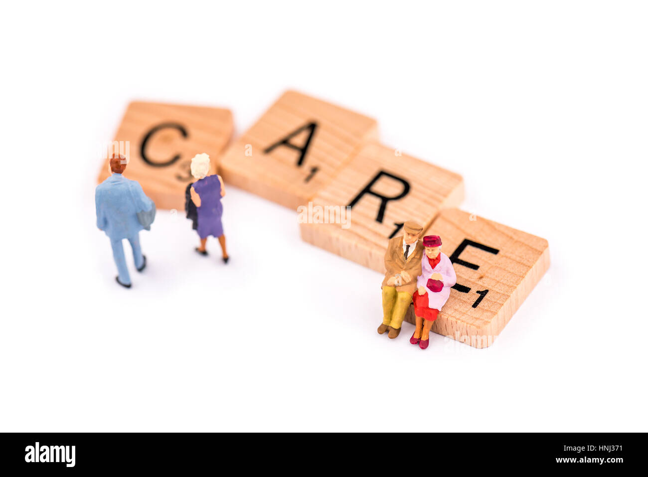 Scrabble letters make up the word CARE. An elderly couple sit on the letter E of the word CARE as a younger couple - Stock Image
